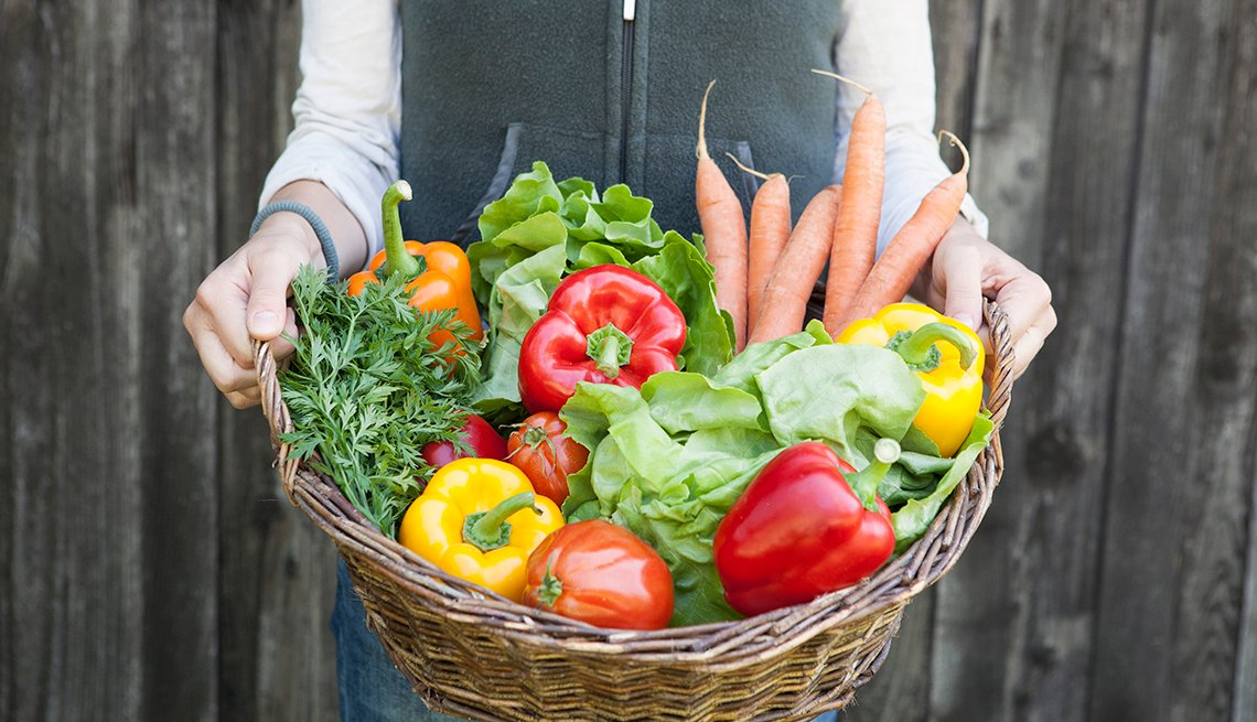 Mujer sosteniendo una canasta con vegetales