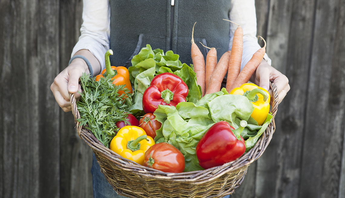 Woman holding a basket with fresh vegetables inside