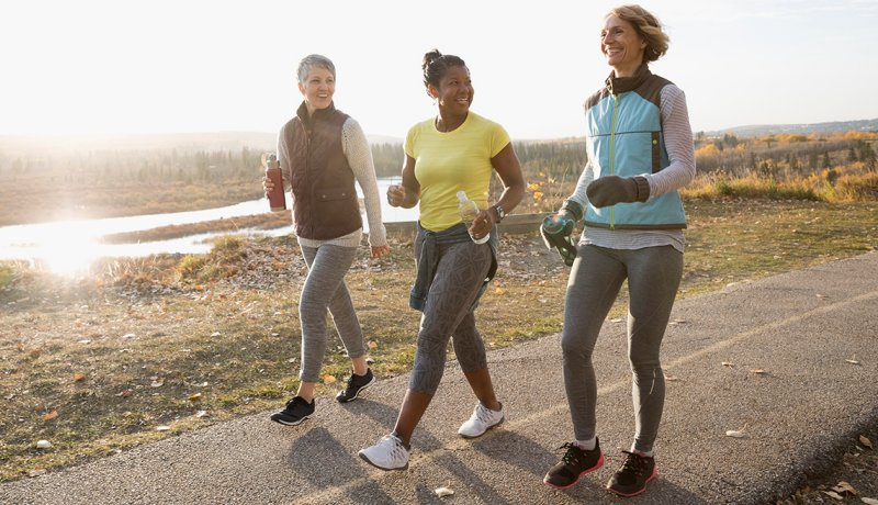 Women power walking exercising on sunny path in autumn park