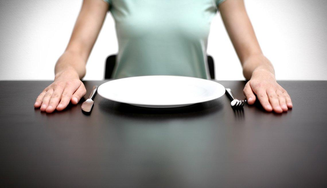 Mujer sentada frente a un plato vacio