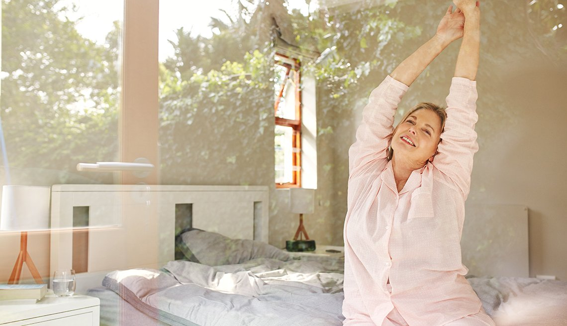 Shot of a mature woman stretching while sitting on her bed