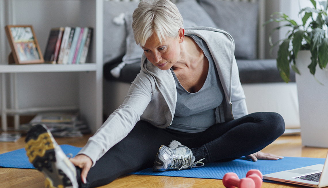Mature woman exercising at home, learning exercises online with laptop. Sitting on floor and stretching.