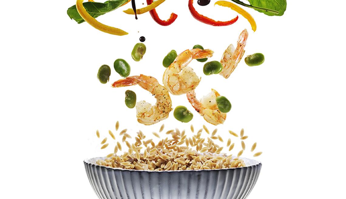 Camarones y vegetales cayendo a un plato hondo