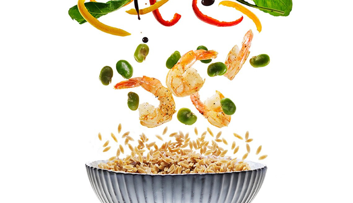 Photo illustration of shrimp and veggies falling in a bowl.