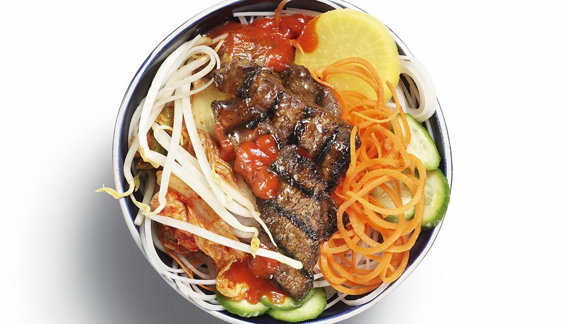 Plato de comida coreana con carne asada, verduras y fideos