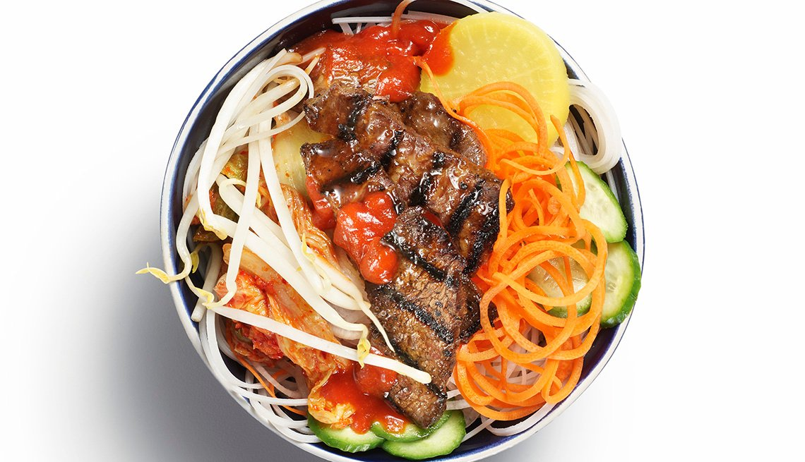 item 1 of Gallery image - Korean food bowl featuring grilled beef, vegetables and noodles.