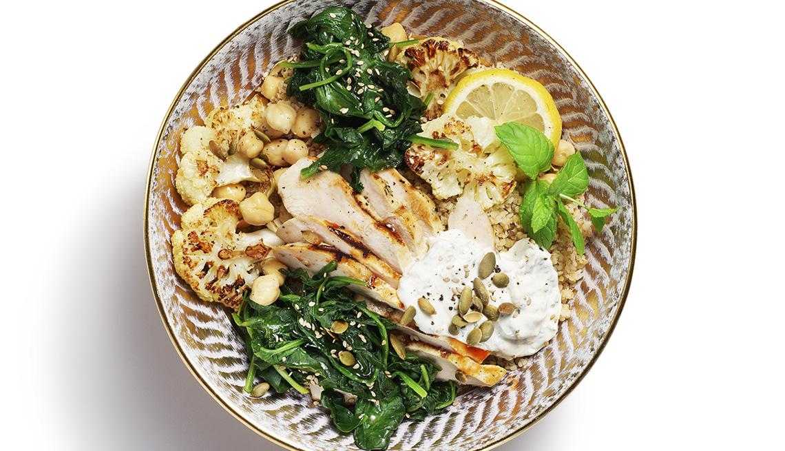 Un plato de comida del Medio Oriente con berenjenas, espinacas y guisantes