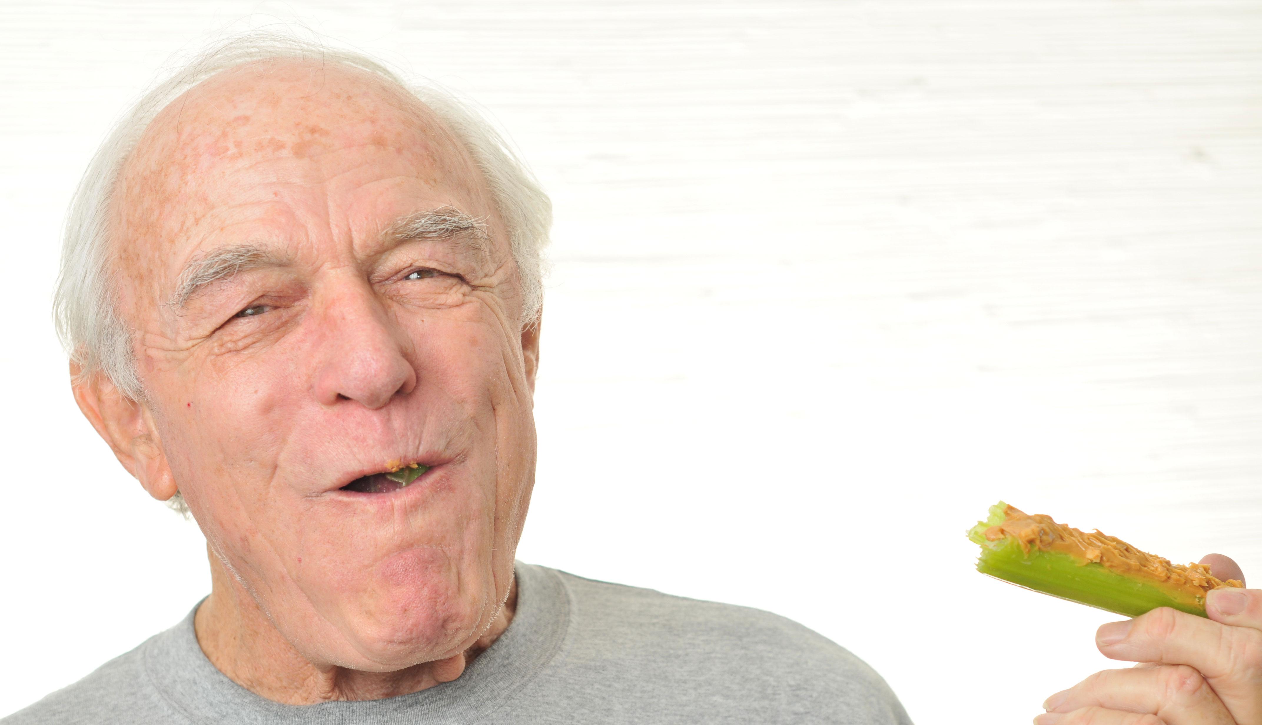 item 9 of Gallery image - Hombre disfruta de un apio con mantequilla de maní