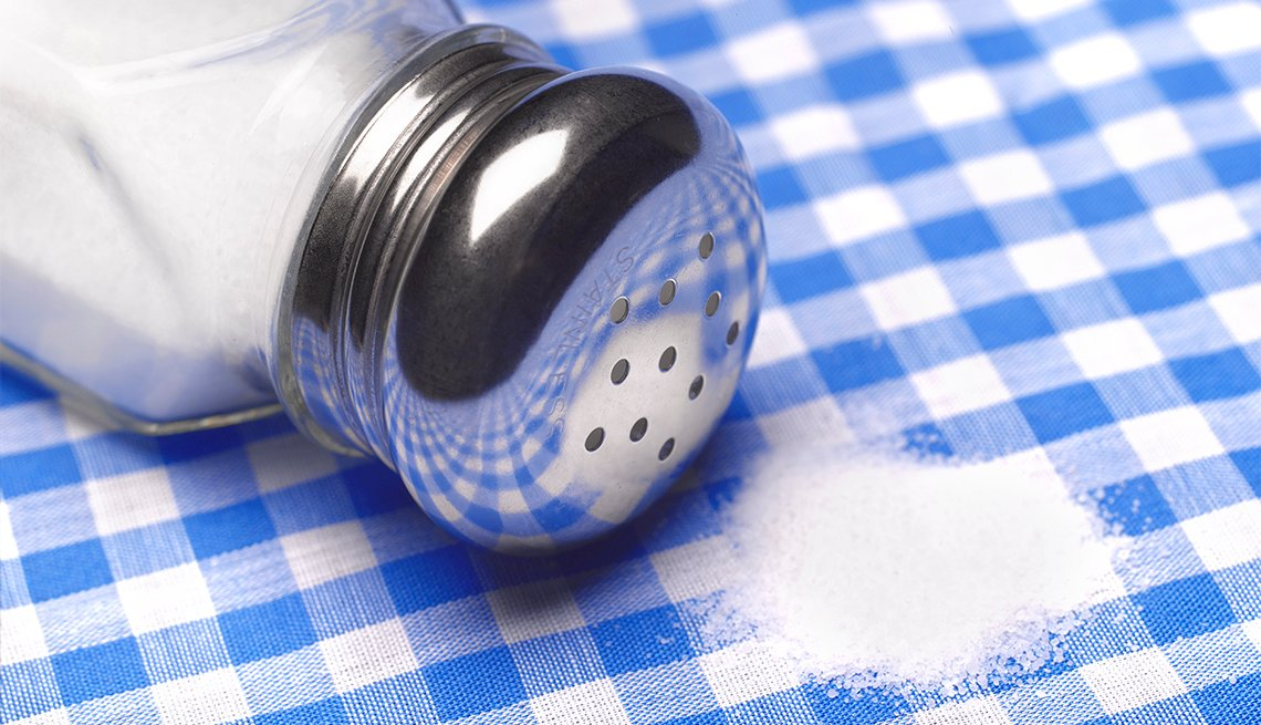 Close up a salt shaker and salt on a table