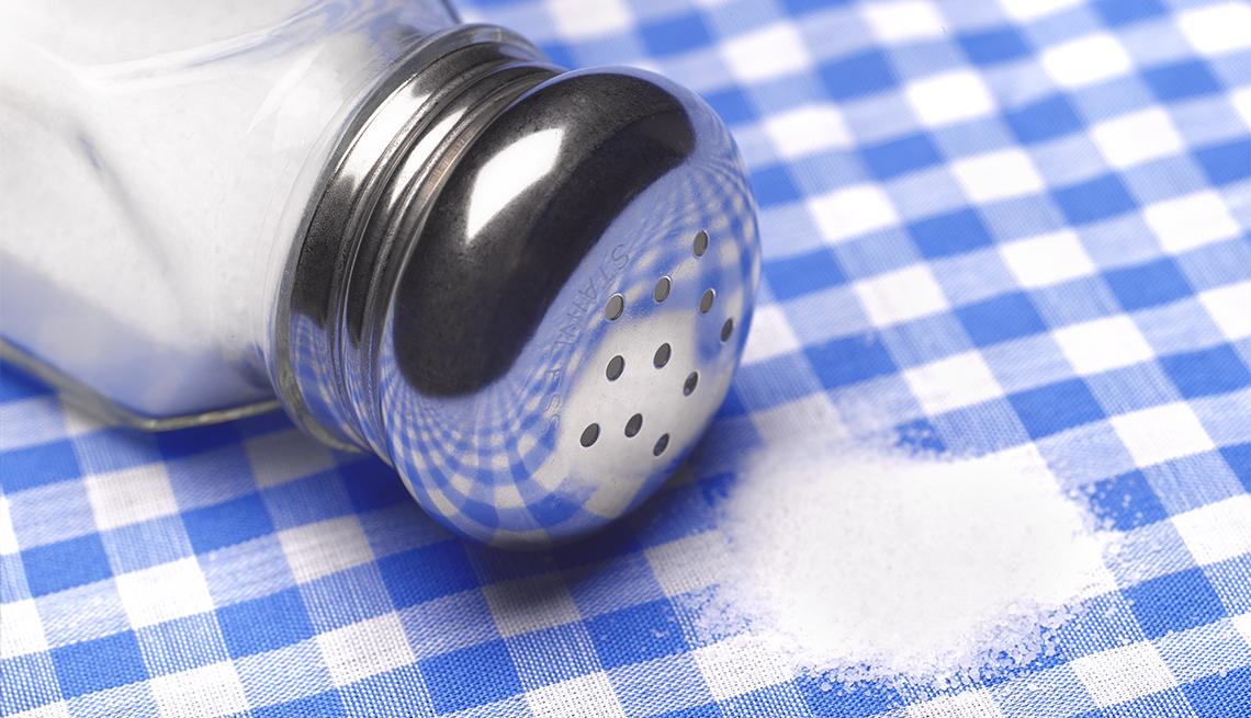 Close up a salt shaker and salt on a table
