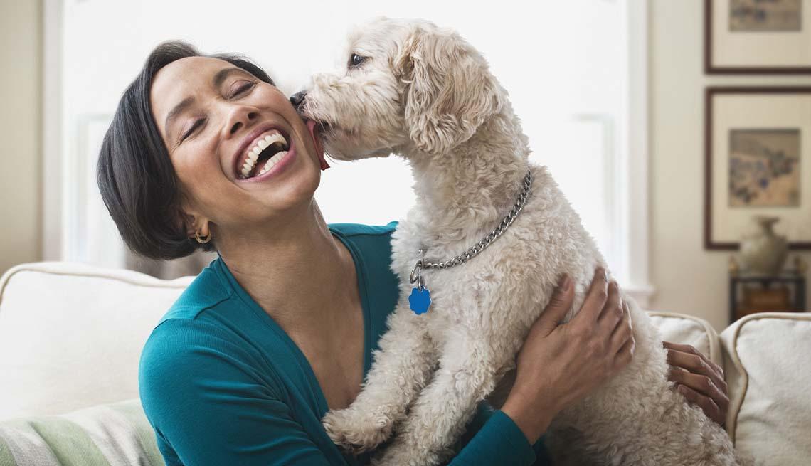 Una mujer se sienta en un sofá con su perro