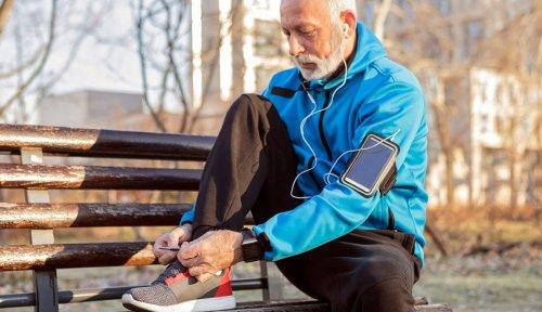 9e9dbf8bcda Older man ties shoe on bench