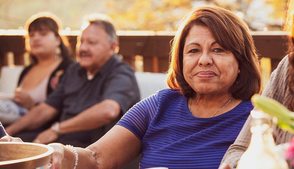 Mujer disfruta de una comida al aire libre con otras personas
