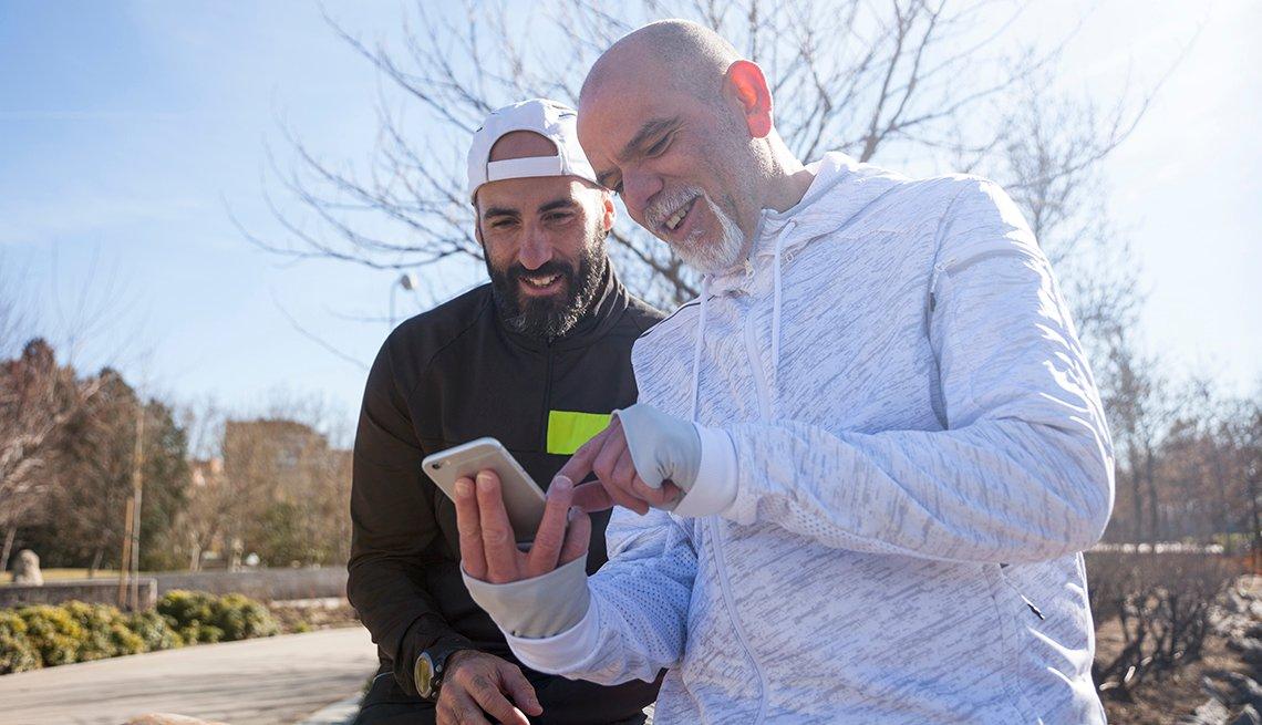 Dos hombres se ejercitan al aire libre mientras miran teléfono