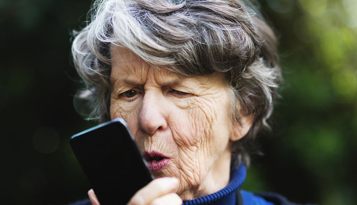Angry senior woman talking to phone