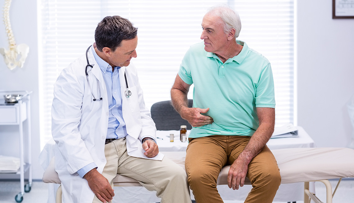 A man shows stomach pain to male doctor