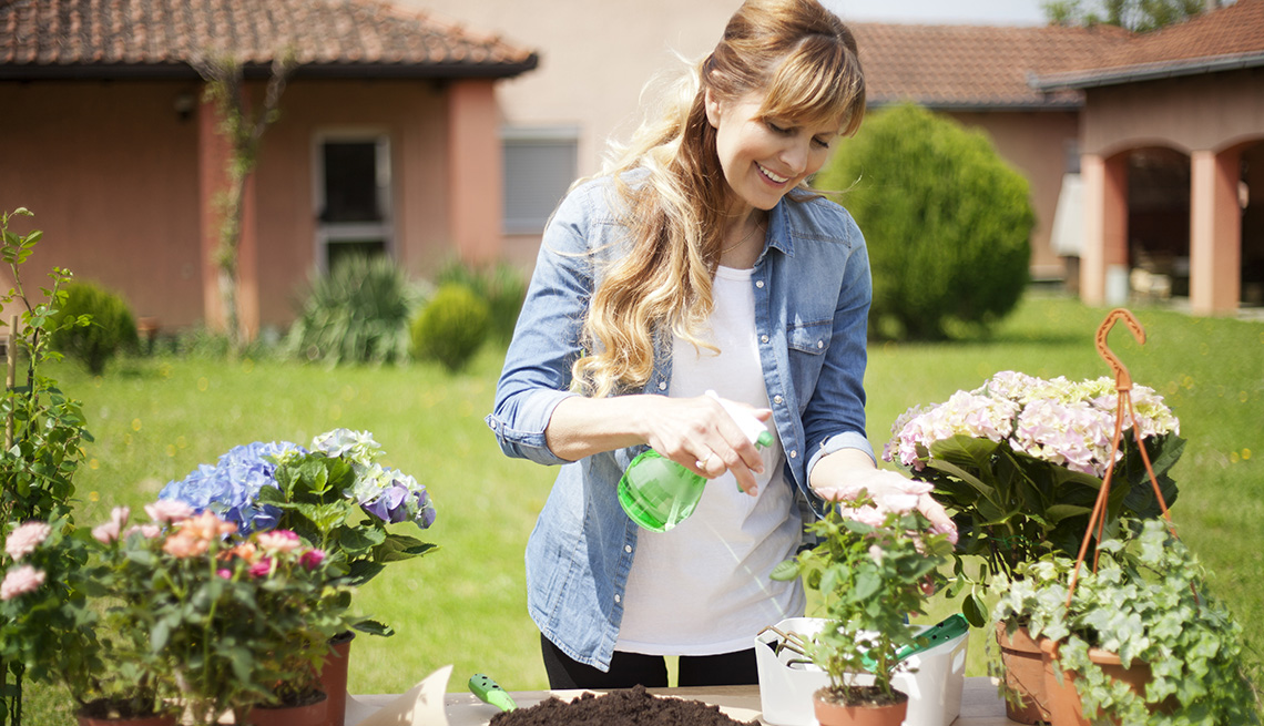 A woman outside her house using a spray bottle to water her flowers