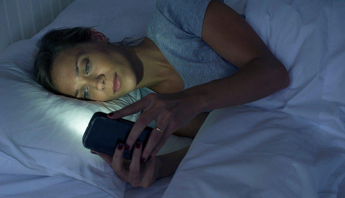 Una mujer acostada en su cama usando su teléfono