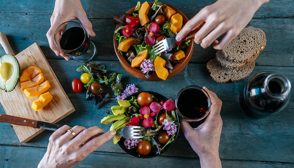 Dos personas cenan ensalada, frutas, pan integral y vino