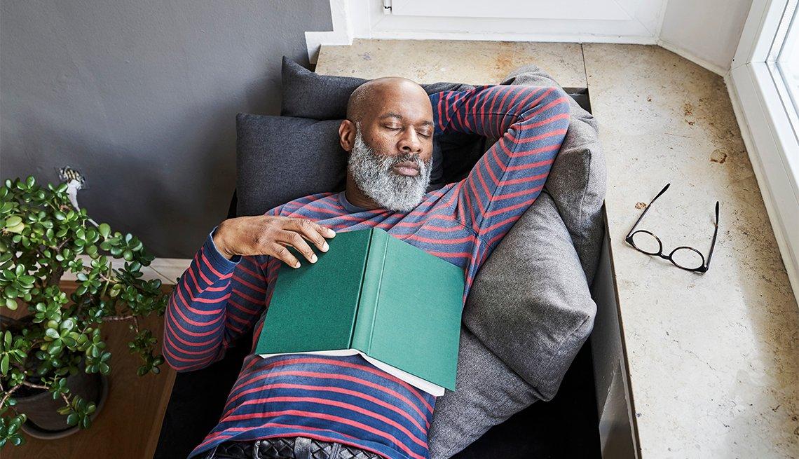 Un hombre toma una siesta en un sofá