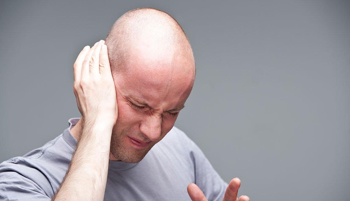 Hombre cubre su oído en señal de dolor