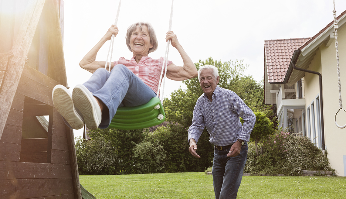 A playful couple playing with a swing in the backyard