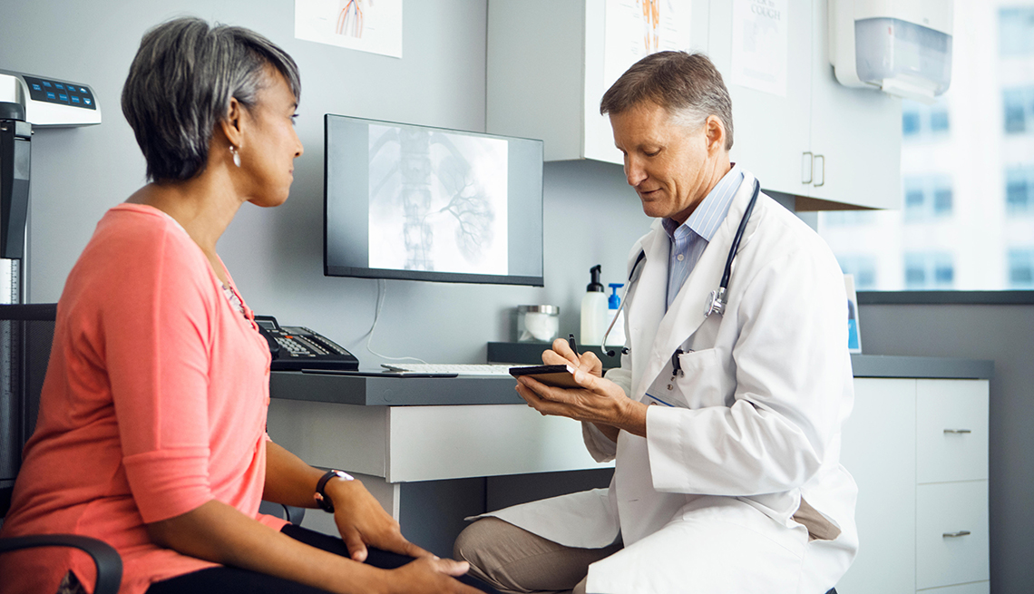 Male doctor writing a prescription for a female patient
