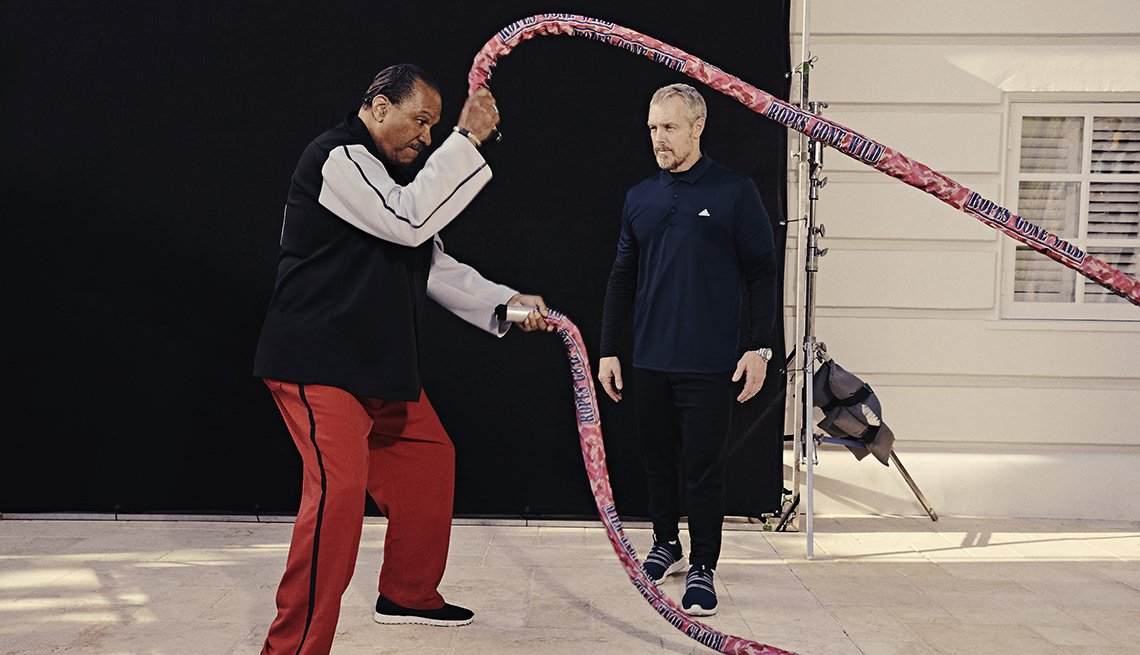 Star Wars actor Billy Dee Williams performing a ropes exercise with a trainer