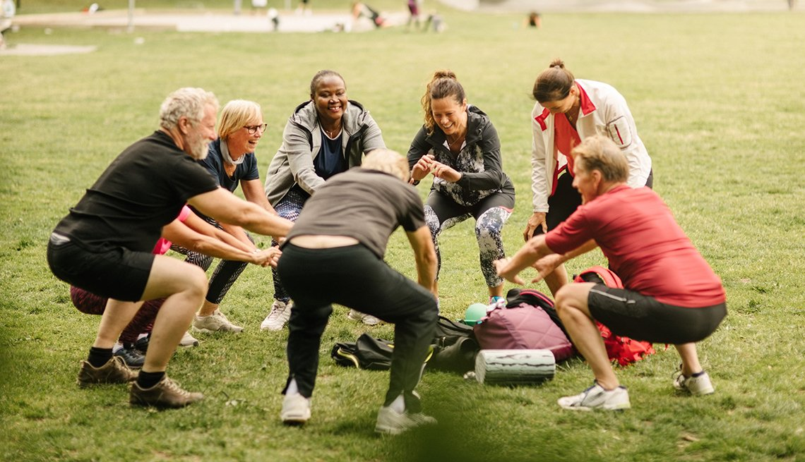 Group of adults in a circle exercising outdoors