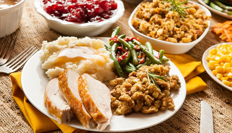A plated holiday turkey dinner with mashed potatoes gravy stuffing green beans and corn