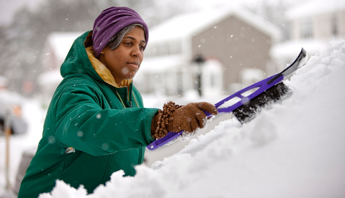 A woman scraping snow from her car's windshield