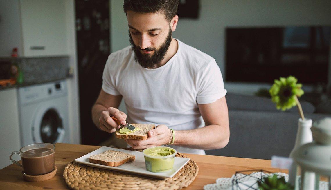 Hombre come tostadas con aguacate