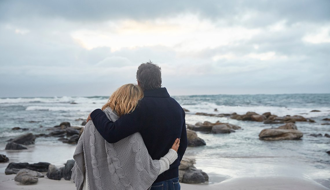 A couple hugging on winter beach looking at the ocean and clouds