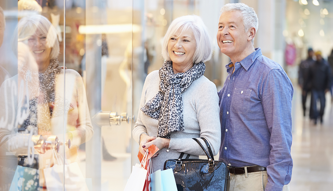 A happy couple looking at a store display while carrying shopping bags in a mall