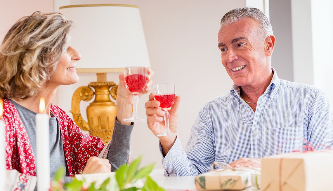 a male and female couple holding glasses with a red beverage
