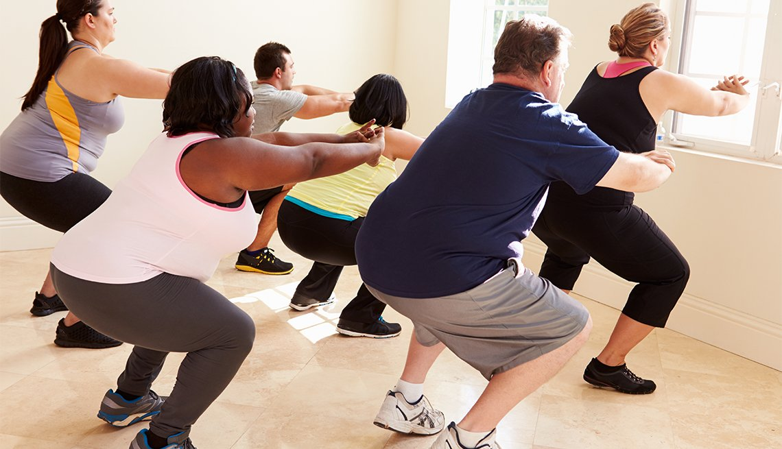 Fitness Instructor In Exercise Class For Overweight People Doing Squats