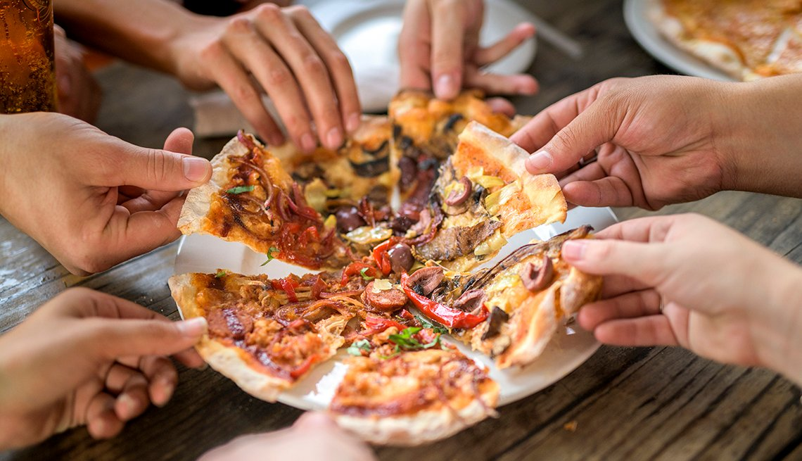 A cropped image showing the hands of a group of friends taking a slice of pizza at a table