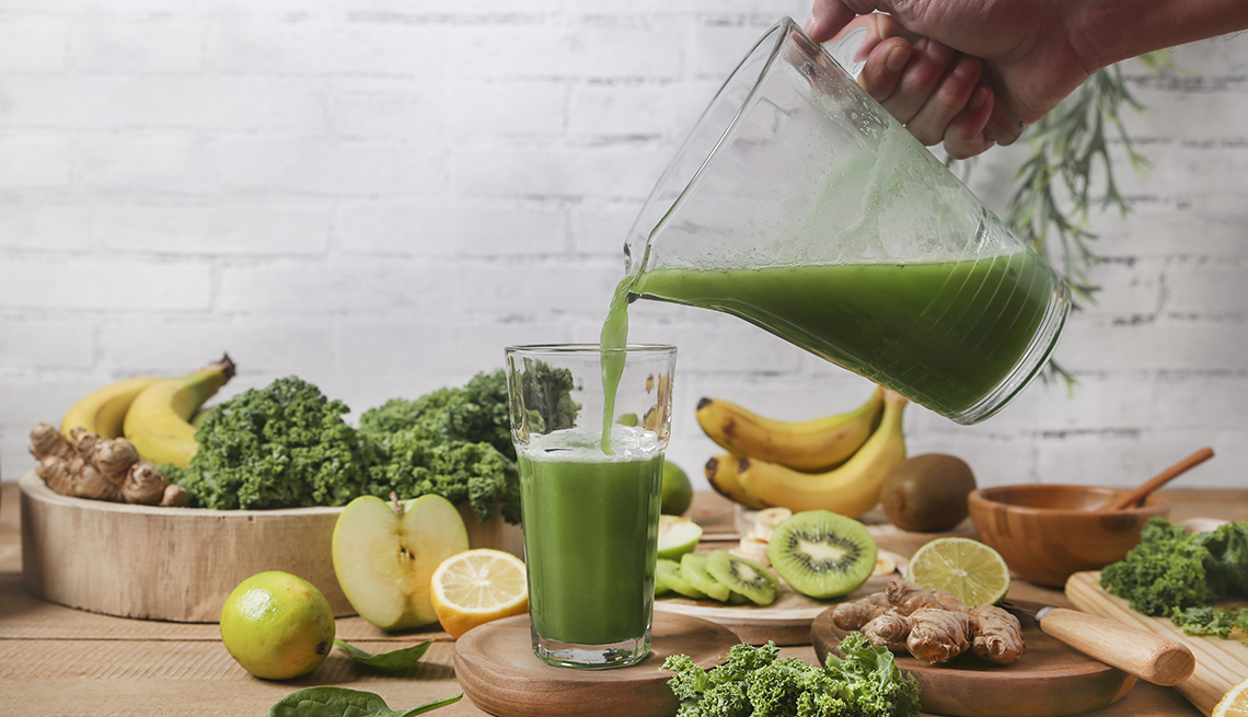 A person pouring green smoothie into a glass which is surrounded by fruits and vegetables