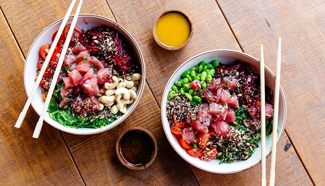 Dos poke bowls servidos con pescado crudo y vegetales