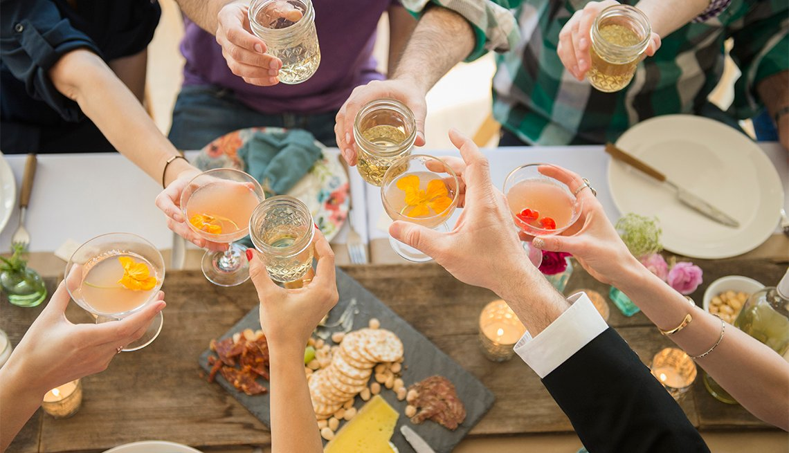 Overhead photo of people holding glasses over table to toast