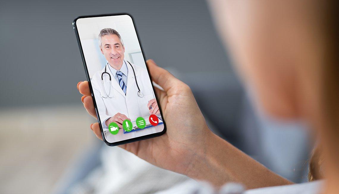 Una persona que tiene una cita de telesalud con un doctor a través del teléfono móvil.