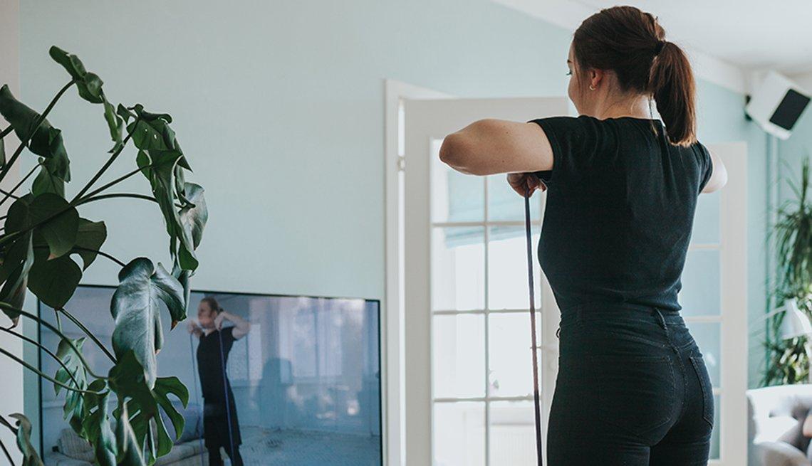 Una mujer haciendo ejercicio mientras mira la computadora.