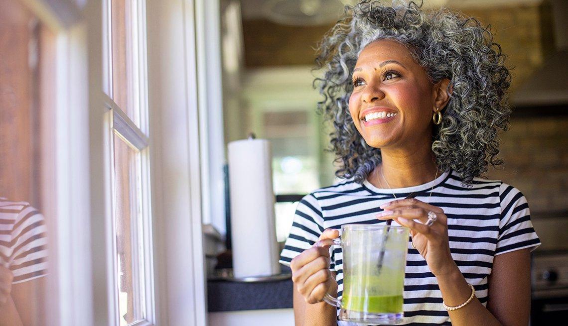 Una mujer bebe un batido verde mientras mira por la ventana.
