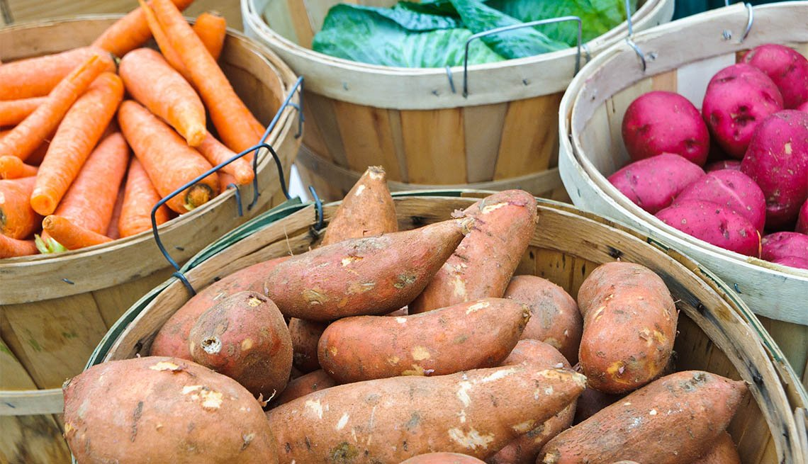 Bushel baskets of carrots, cabbage, red and sweet potatoes offered for sale and a midwinter farmers market on Cape Cod