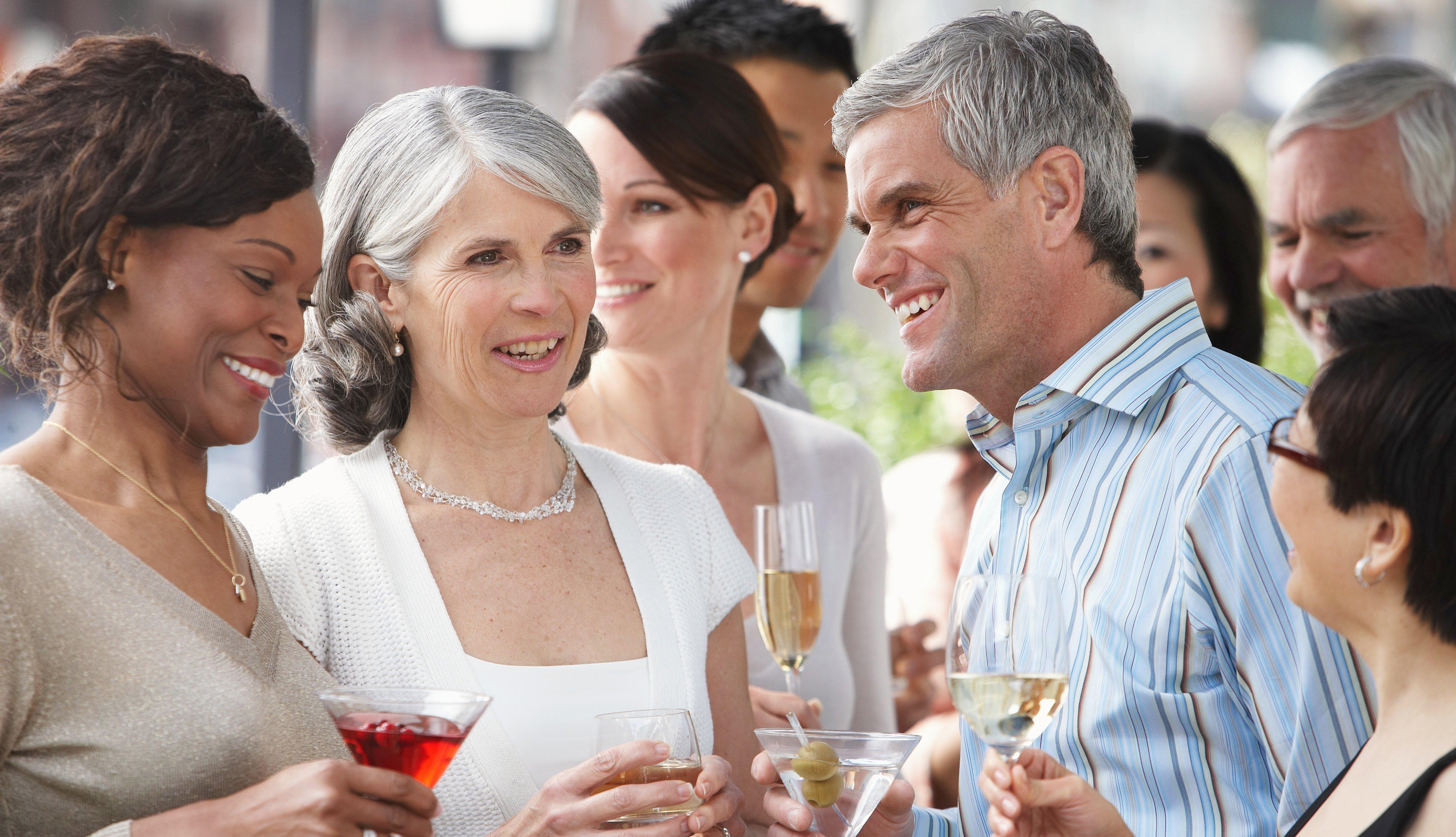 Grupo de adultos socializando mientras toman alcohol