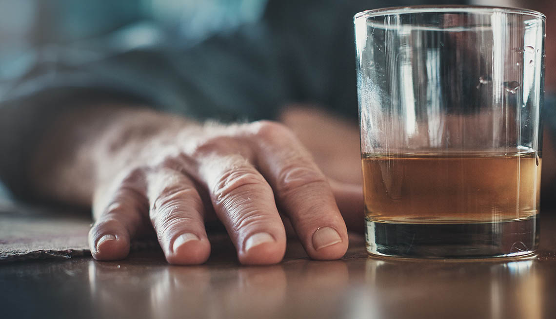 Mano de un hombre y un vaso con licor
