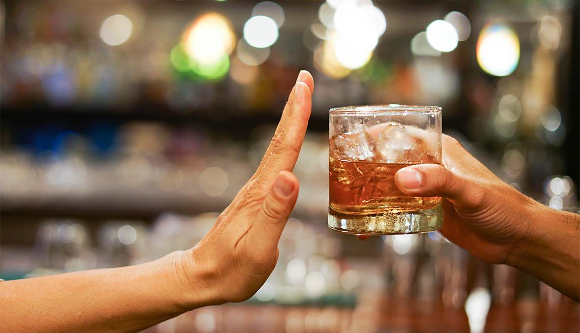 Una mano en señal de detente mientras otra mano le ofrece un vaso con alcohol