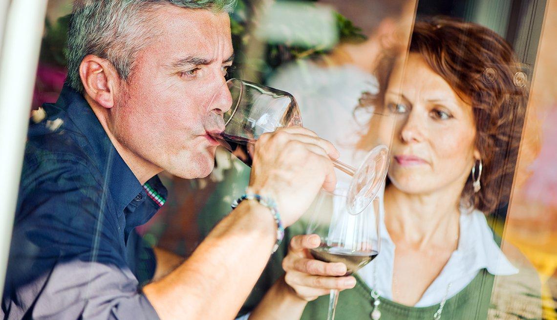 Un hombre maduro toma una copa de vino mientras una mujer lo observa
