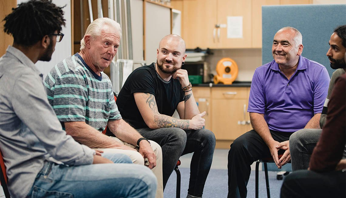 Diverse group of men are talking and laughing together in an alcoholism support group.