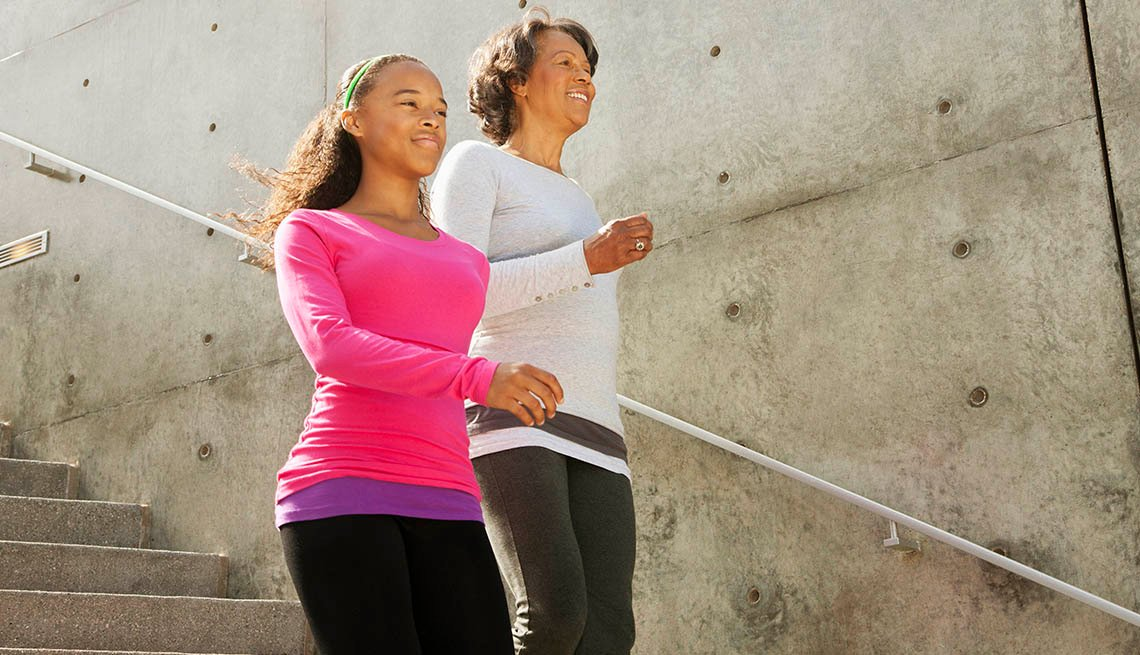 A mother and daughter, both African American walk down stairs outside as they exercise